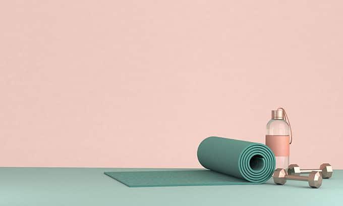 Yoga mat, water bottle and dumb bells on the floor.